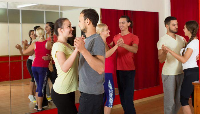 Group of  people dancing rumba in studio